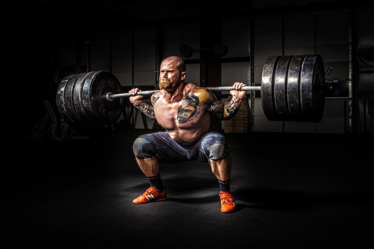 Bodybuilding Harm Your Joints shirtless man squatting heavy weight