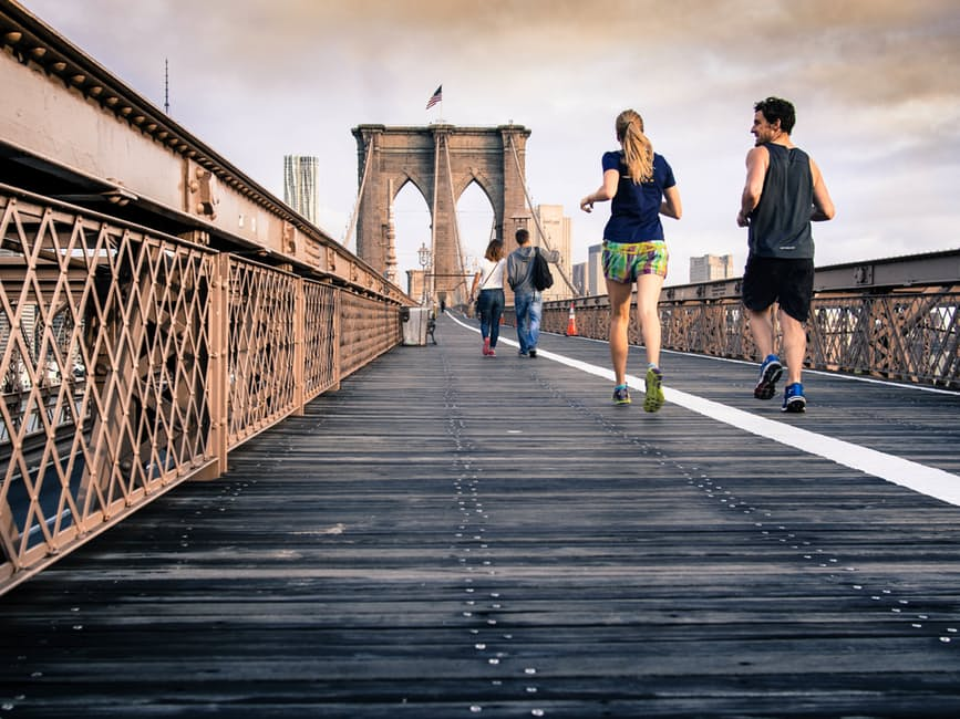 Fitness Partner couple running on bridge