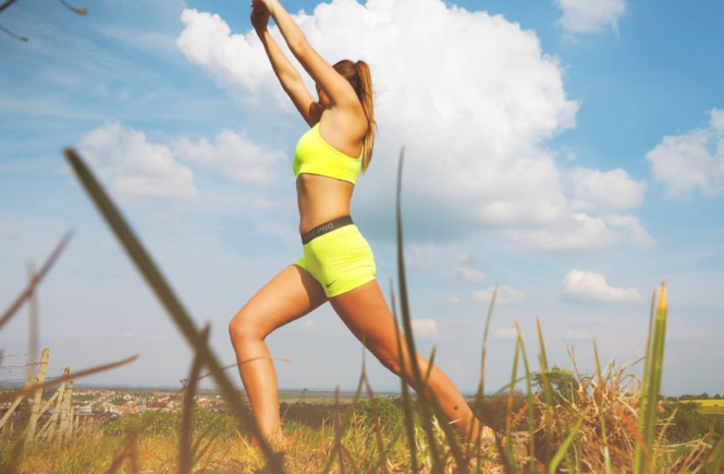 Losing Weight woman stretching in outdoor field