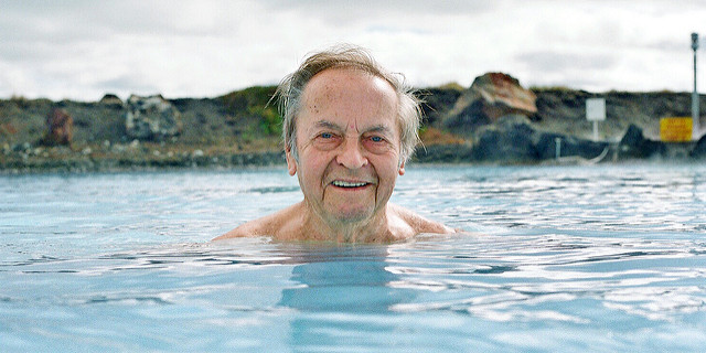Senior man swimming in pool smiling