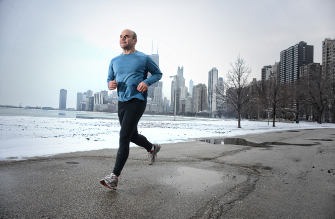 Fitness man running along city lakeshore
