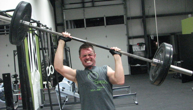 Fitness Setbacks man lifting barbell over head
