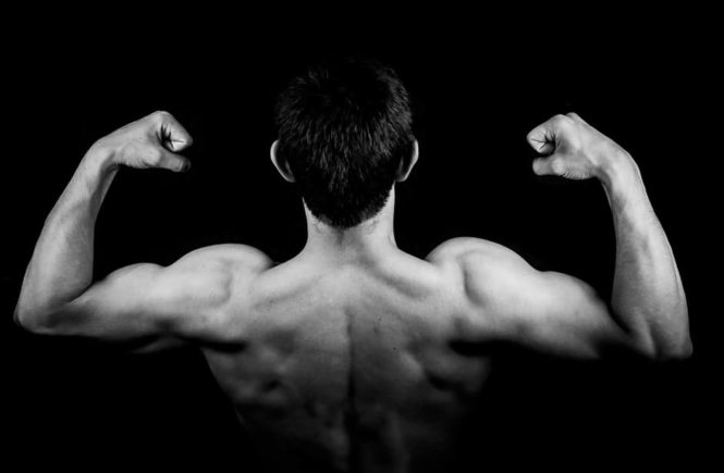 man back building muscle in dark