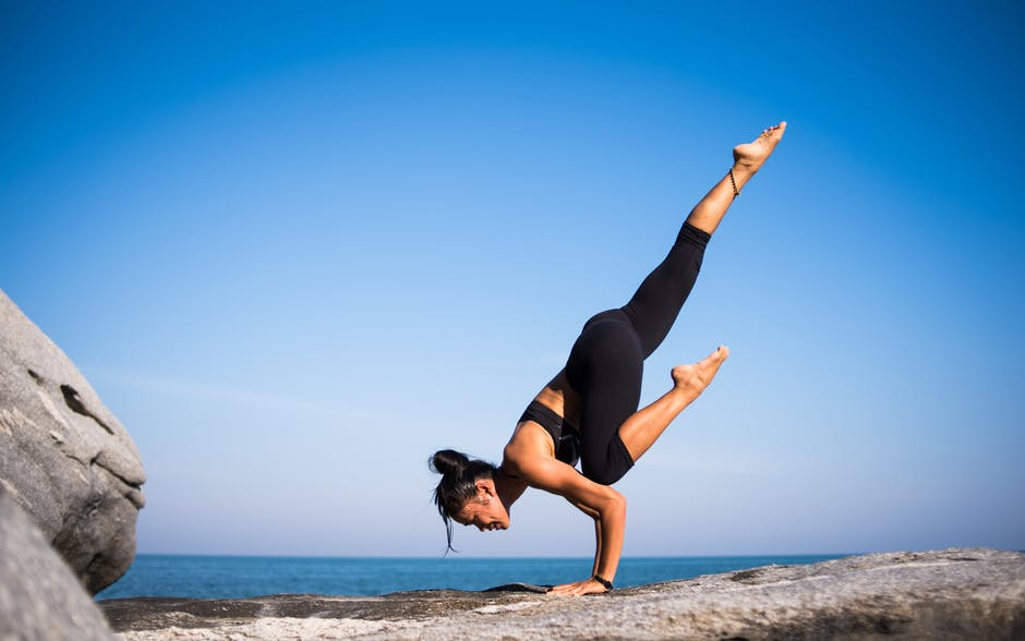 woman balancing on hands on cliff