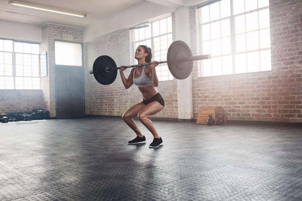 Bodybuilding woman squatting barbell