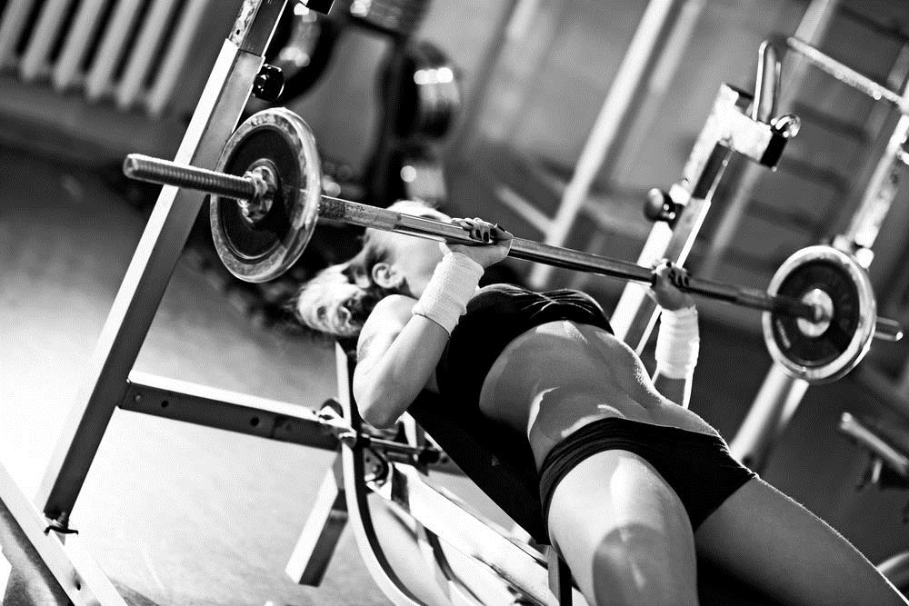Bodybuilding woman bench pressing barbell weights