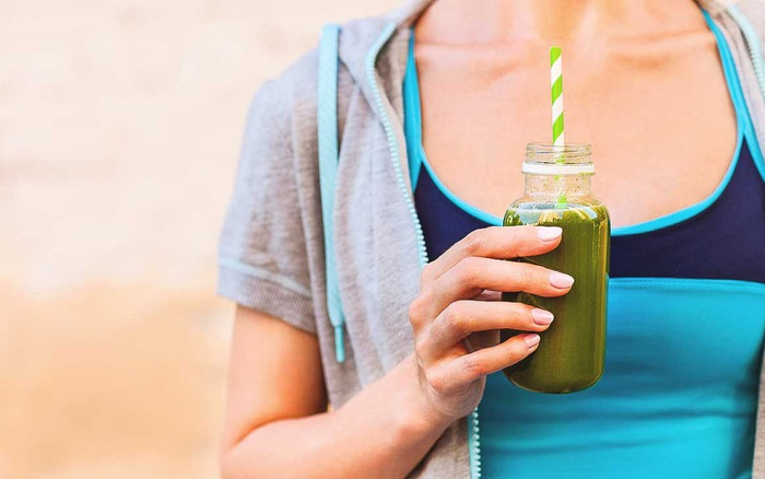 Detox Drinks woman holding smoothie in hand
