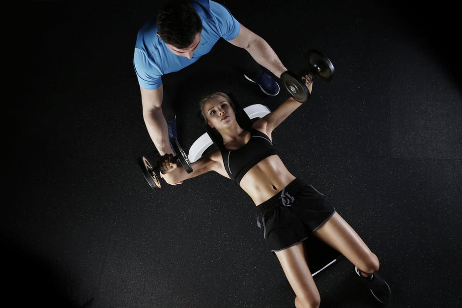 woman bench pressing in dark with male spotter