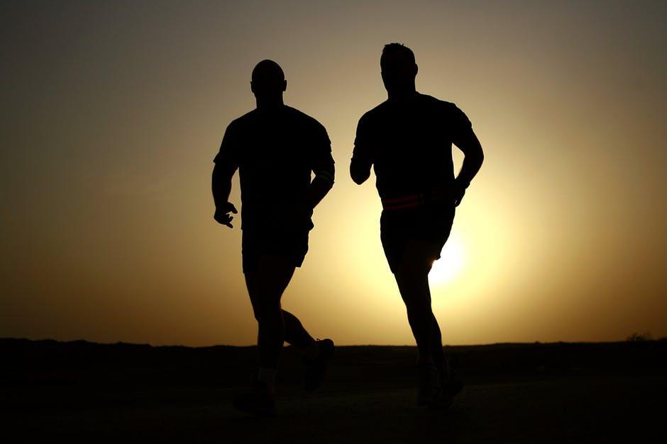 Fitness men running in the sunset