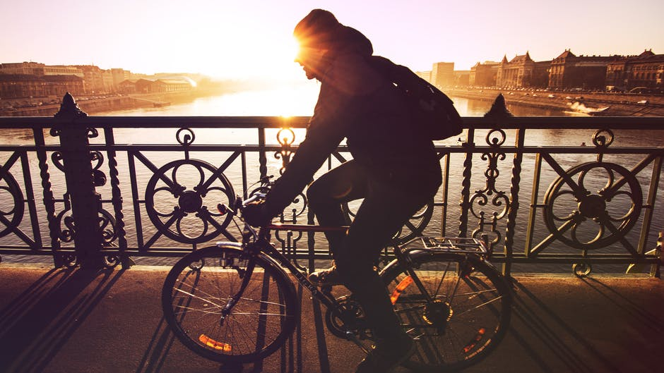 Avoid Hip Replacement man biking across bridge