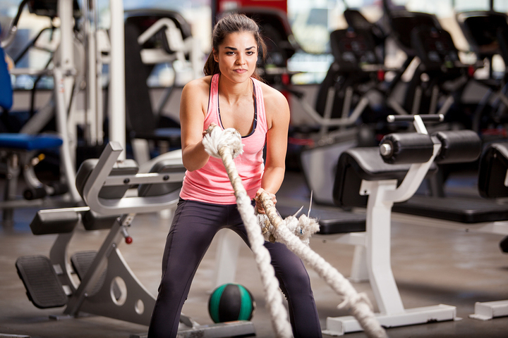 Pretty Hispanic young woman doing some crossfit exercises with a rope at a gym